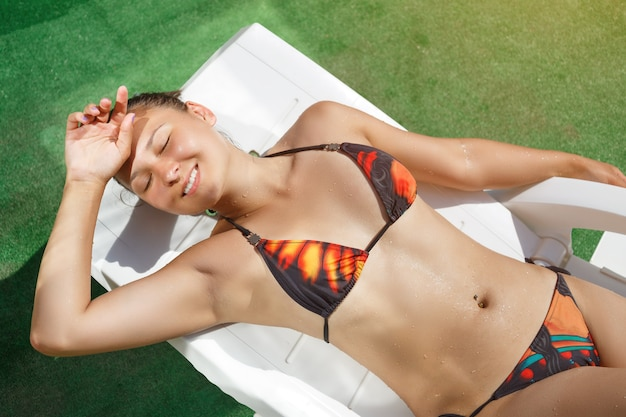 Young woman sunbathing on a sun lounger under the bright sun