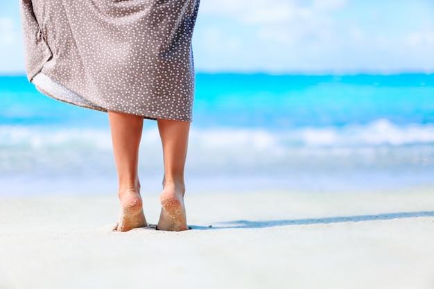 Young woman sunbathing on white beach. legs.