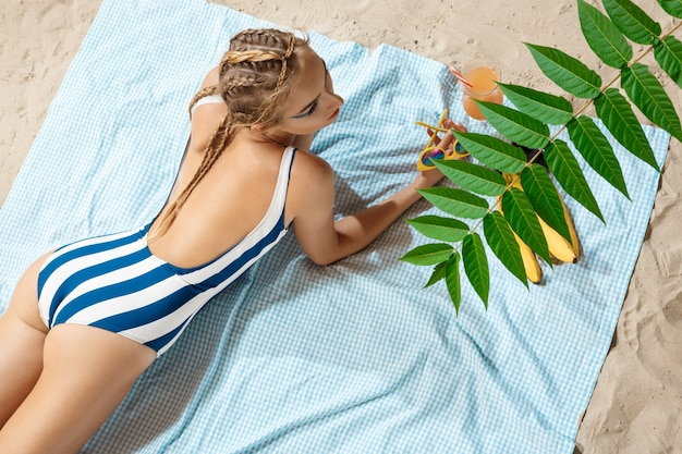 Young woman sunbathing with striped swimwear