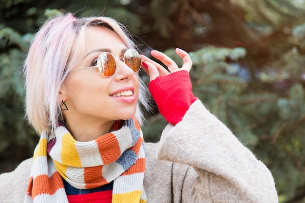Young woman in sunglasses on a background of fir tree
