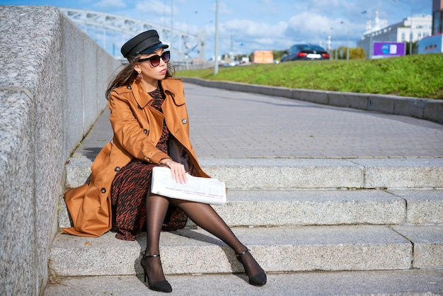 Young woman in sunglasses of caucasian ethnicity sits on the steps on the embankmen