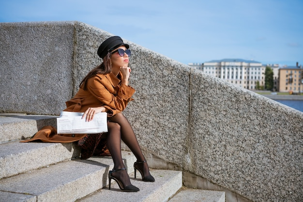 Young woman in sunglasses of caucasian ethnicity sits on the steps on the embankment in a black cap and brown jacket with a newspaper in her hand