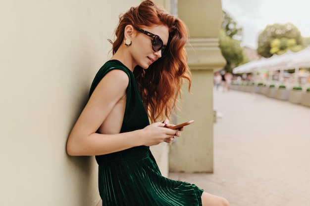 Young woman in sunglasses chatting on phone and leaning on wall