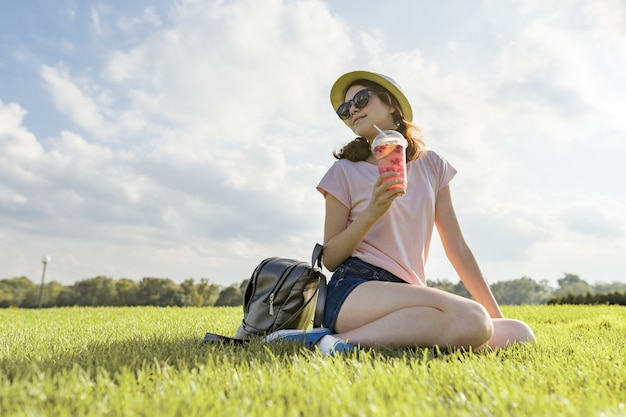 Young woman in sunglasses and hat drinks summer berry drink