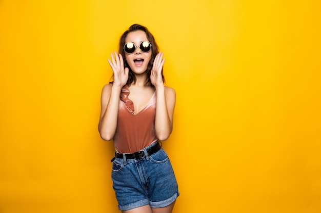 Young woman sunglasses looking away with surprised smile isolated on yellow wall.