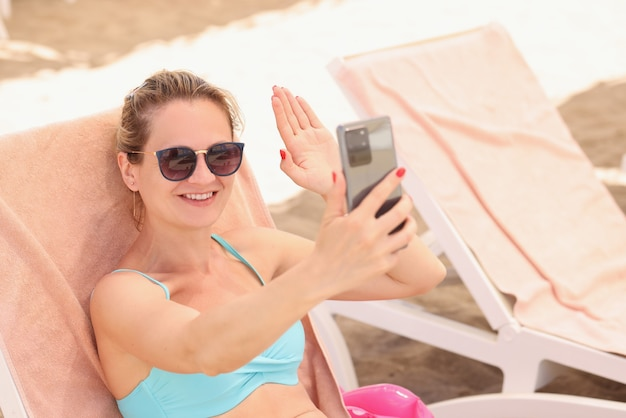 Young woman in sunglasses lying on beach lounger and waving at screen of mobile phone
