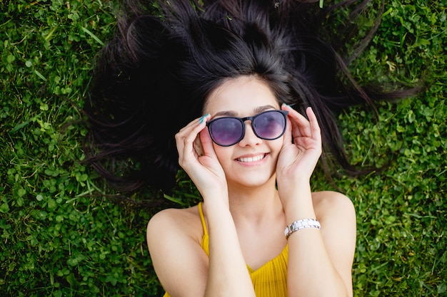 Young woman in sunglasses lying on a green lawn and smiling, top view