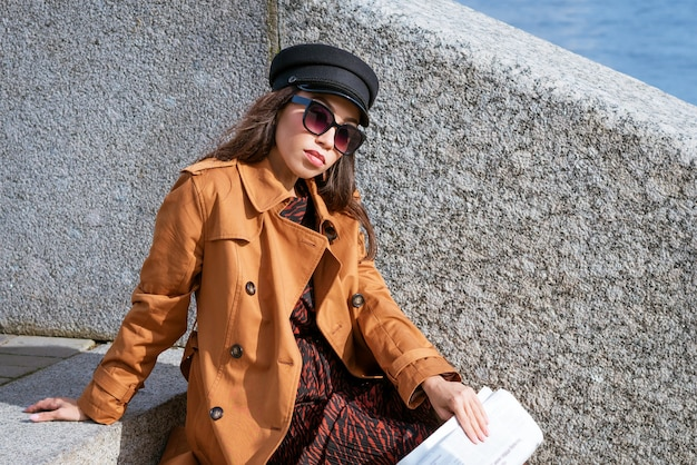 Young woman in sunglasses sits on the steps on the embankment in a black cap and brown jacket with a newspaper in her hand