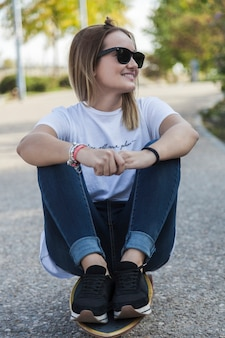 Young woman in sunglasses sitting on longboard