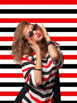 Young woman in sunglasses on stripes background