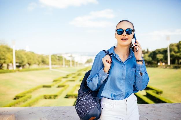Giovane donna in occhiali da sole a parlare su un cellulare su uno sfondo di piante