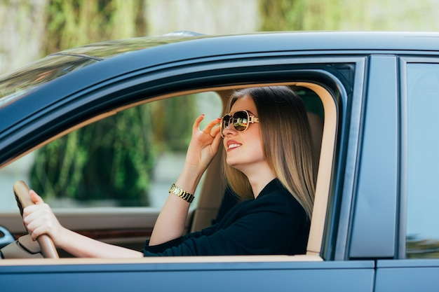 Young woman in sunglasses behind the wheel