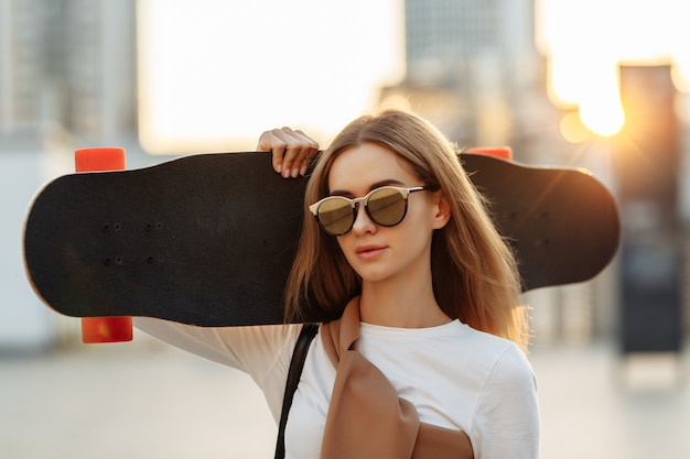 Young woman in sunglasses and with a cat on his shoulder. high quality photo
