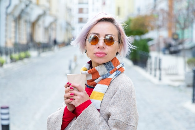 Young woman in sunglasses with a cup of coffee