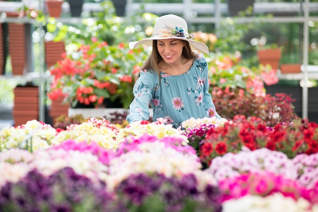 Young woman in sunhat buying plants at a nursery