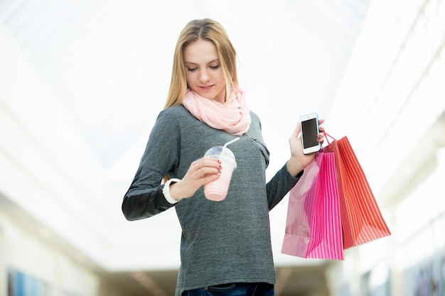 Young woman in supermarket checking time holding shopping bags, cellphone and a drink