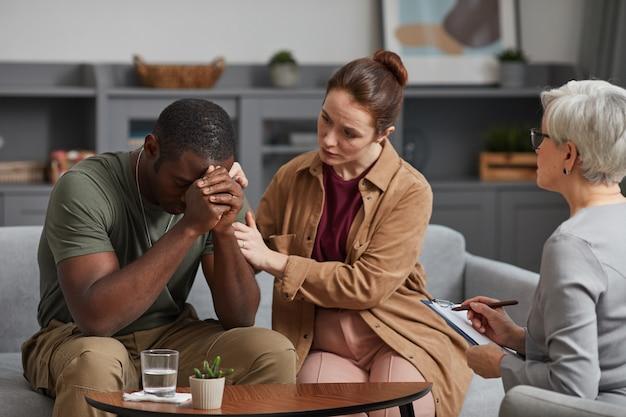 彼らが心理学者を訪問している間、落ち込んでいるアフリカの男性をサポートする若い女性