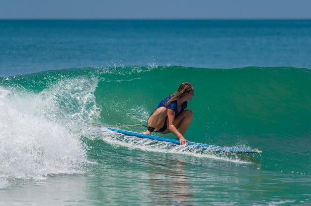 해변에서 서핑하는 젊은 여자