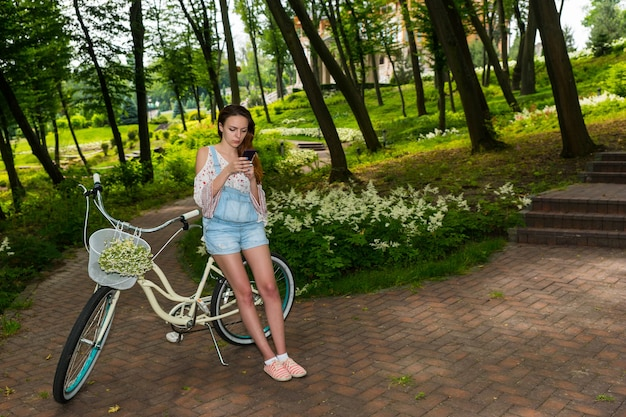 公園や森のバスケットに小さな白い花の花束を持って自転車に寄りかかってスマートフォンでインターネットサーフィンをしている若い女性