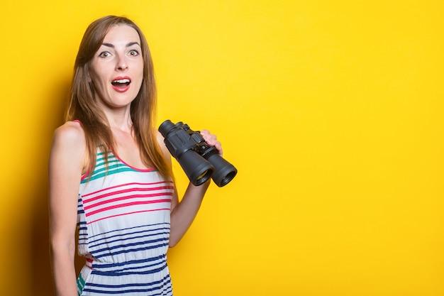 Удивленная шок молодая женщина в полосатом платье держит бинокль на желтом пространстве.