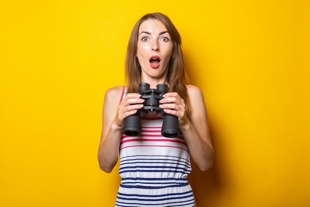 Young woman surprised shock in a striped dress holds binoculars on a yellow space