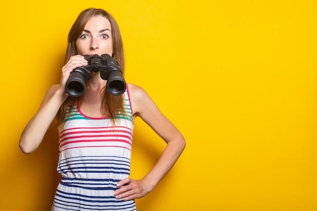 Young woman surprised shock in a striped dress holds binoculars on a yellow space.