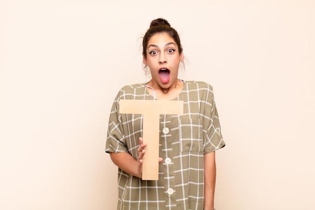 Молодая женщина удивлена, шокирована, поражена, держа букву т алфавита, чтобы образовать слово или предложение.