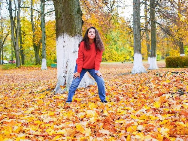 公園の黄色い落ち葉に囲まれた若い女性