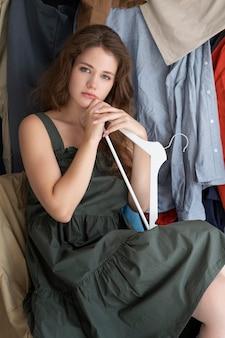 Молодая женщина в окружении груды одежды
