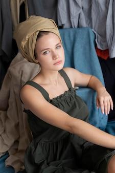 옷 더미에 둘러싸인 젊은 여자