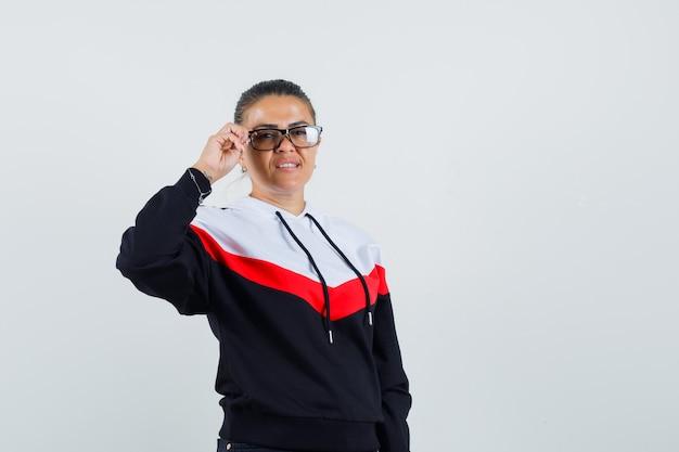 Giovane donna in maglione e jeans neri che tengono gli occhiali con una mano e che sembra felice, vista frontale.