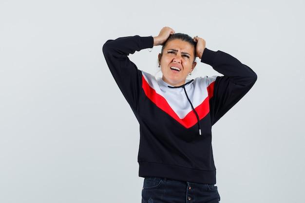 Giovane donna in maglione e jeans neri che tengono le mani sulla testa, guardando verso l'alto e guardando tormentato, vista frontale.