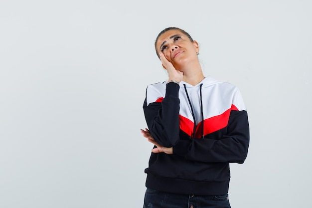 Giovane donna in maglione e jeans neri appoggiato la guancia sul palmo e pensando a qualcosa e guardando pensieroso, vista frontale.