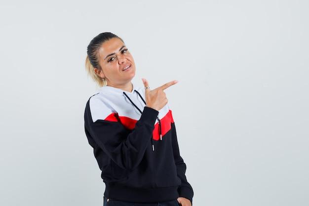 Giovane donna in maglione e jeans neri che punta a destra con il dito indice e sembra carina, vista frontale.