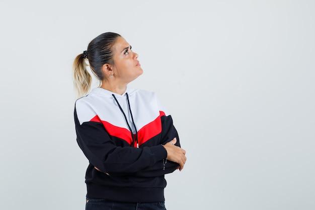 Giovane donna in maglione e jeans neri in piedi con le braccia incrociate, guardando lontano e guardando piuttosto, vista frontale.