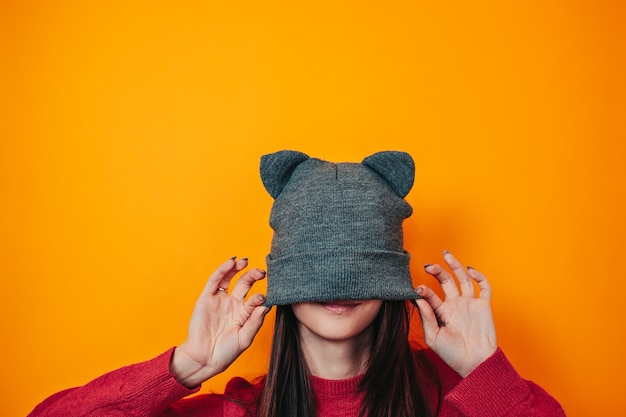Young woman in sweater and hat with ears. winter clothes. hat on face.