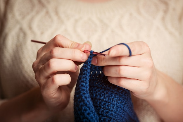 Young woman in sweater knitting with crochet hook