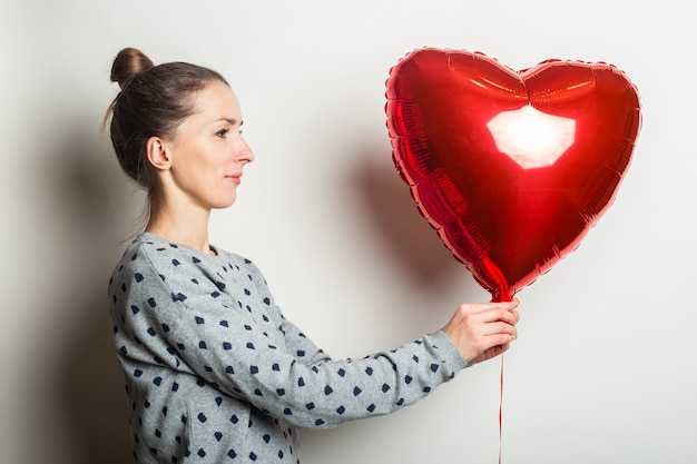 Young woman in a sweater looks at the heart air balloon on a light background. valentines day concept.