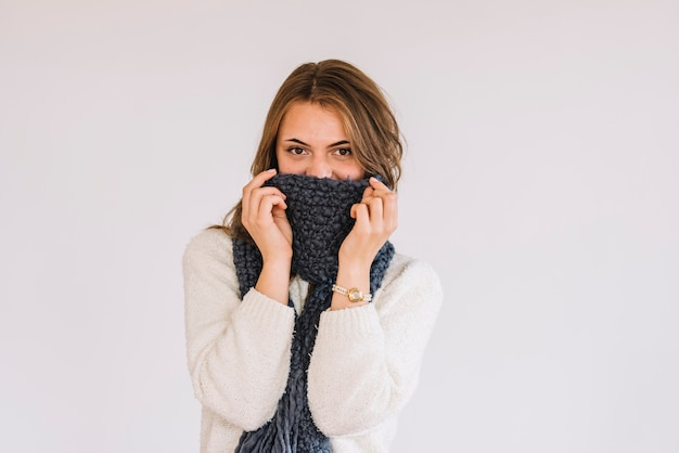 Young woman in sweater and scarf on face