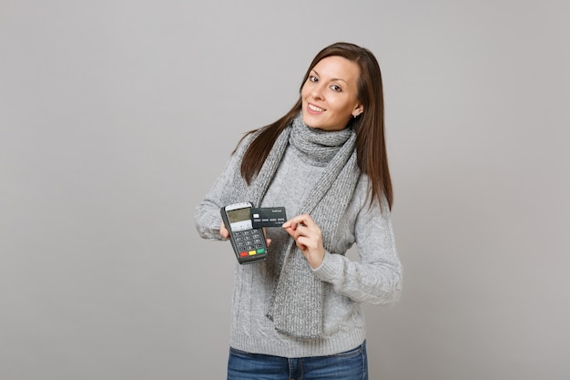 Young woman in sweater, scarf hold wireless modern bank payment terminal to process, acquire credit card payments isolated on grey background. lifestyle, people sincere emotions, cold season concept.