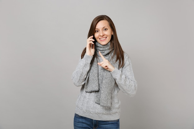 Young woman in sweater, scarf pointing index finger talking on mobile phone conducting pleasant conversation isolated on grey background. healthy fashion lifestyle people emotions cold season concept.