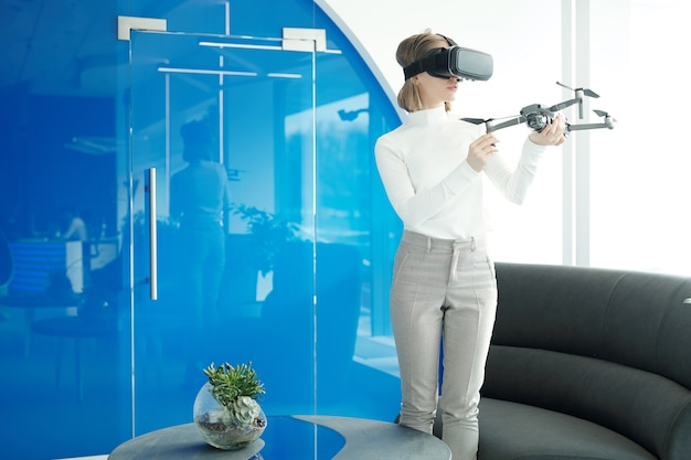 Young woman in sweater standing in modern lobby and operating drone with virtual reality device