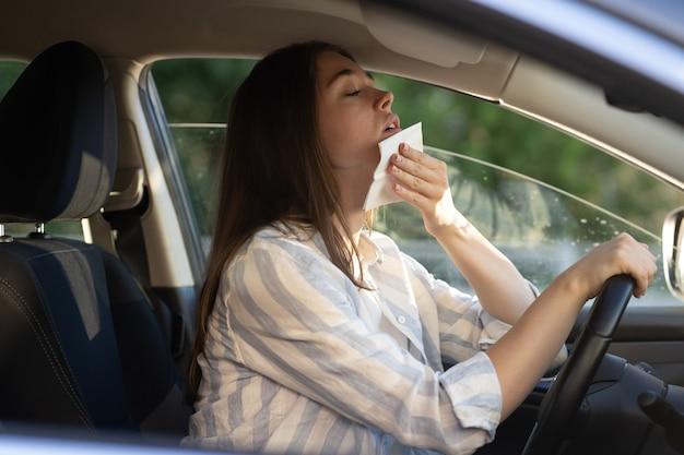땀을 흘리는 젊은 여성은 열사병으로 에어컨이 고장난 열 드라이브 자동차 소녀 드라이버로 고통받습니다.