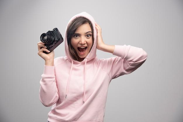 Giovane donna in felpa tenendo la fotocamera felicemente.