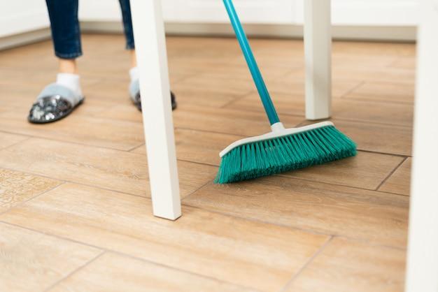 若い女性は、明るいキッチンでラミネートフローリングを掃引します。女の子は白いキッチンテーブルの下からほこりや汚れを掃除します
