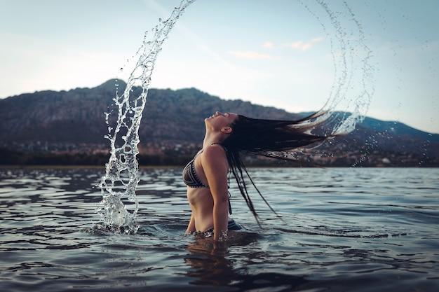 일몰에 호수에서 수영하는 젊은 여자