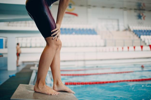 競争の準備をし、プールで泳ぐ若い女性スイマー