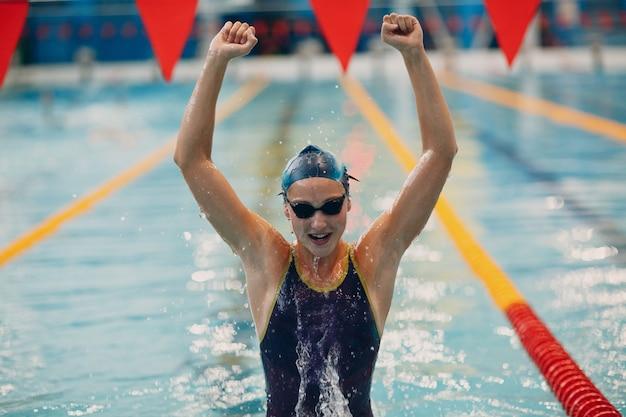 若い女性のスイマーの肖像画の喜びは、スイミングプールでの水泳大会での勝利を喜ぶ