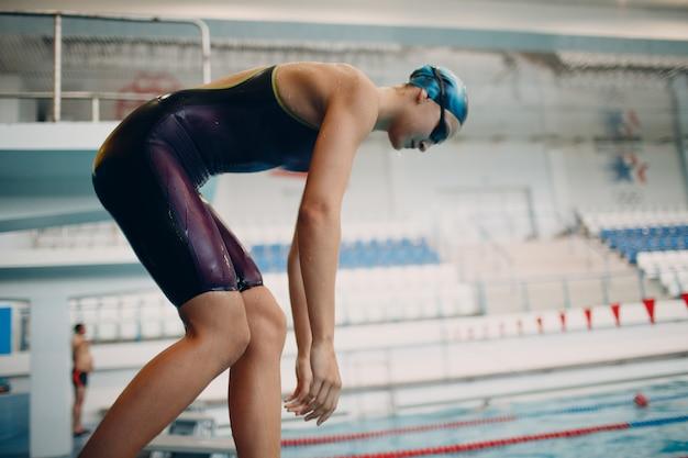 若い女性のスイマーはプールで泳ぐ