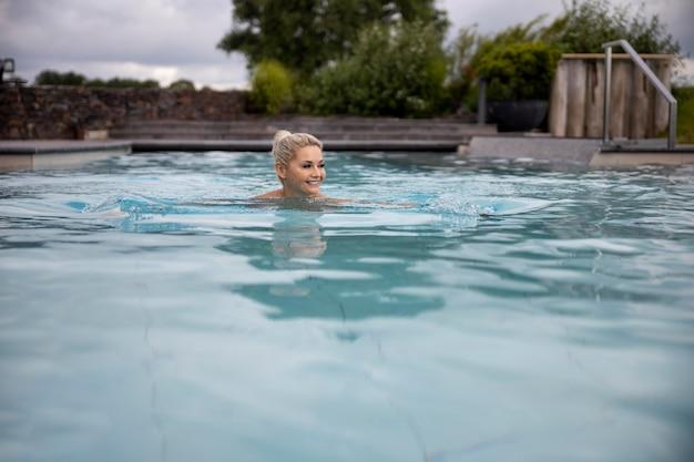 스파 호텔의 수영장에서 수영하는 젊은 여성